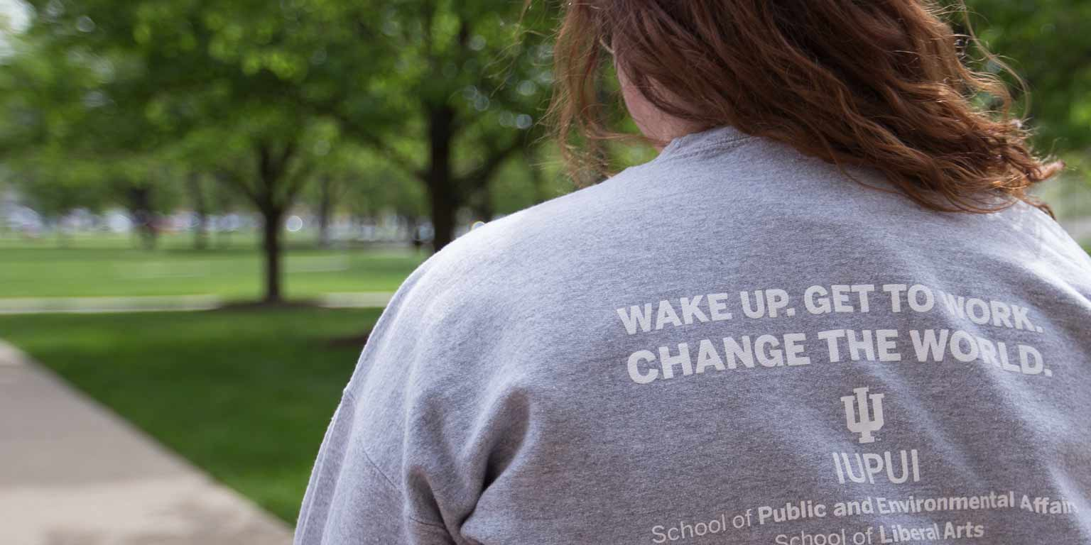A student wears a SPEA shirt that says, 'Wake up. Get to work. Change the world.'