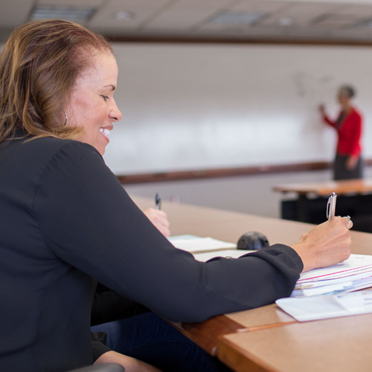 A woman takes notes during an executive education class.