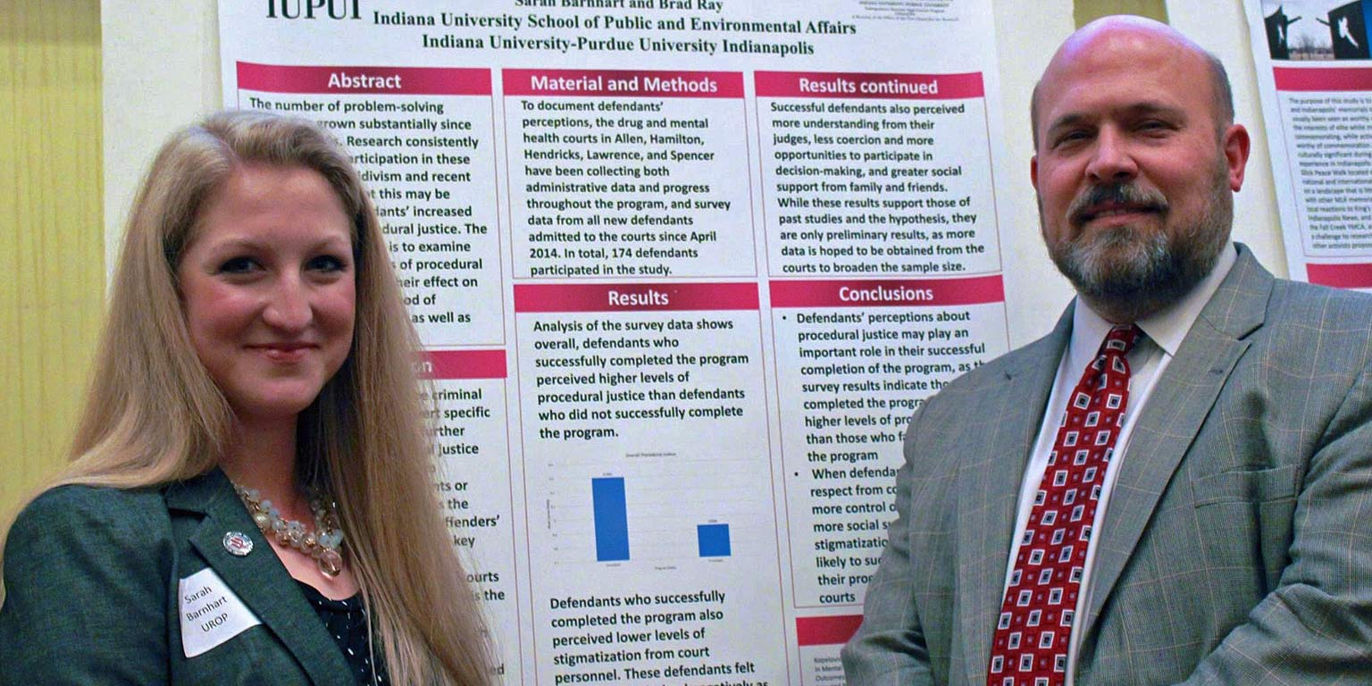 Two researchers present data on a research poster.