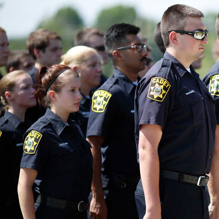 Police cadets stand at attention.