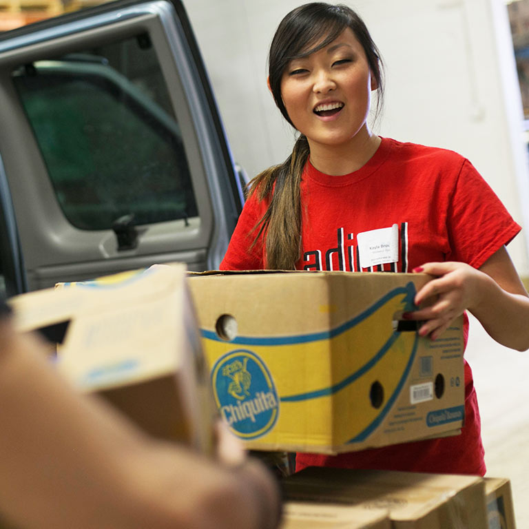 A student volunteer loads donated food into a truck.