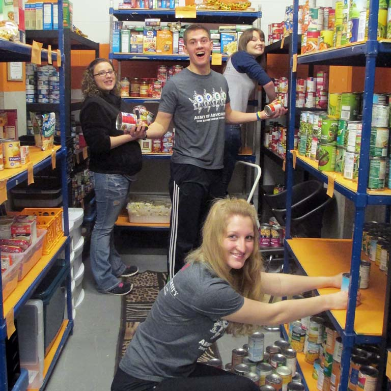 Student volunteers stock a food bank.