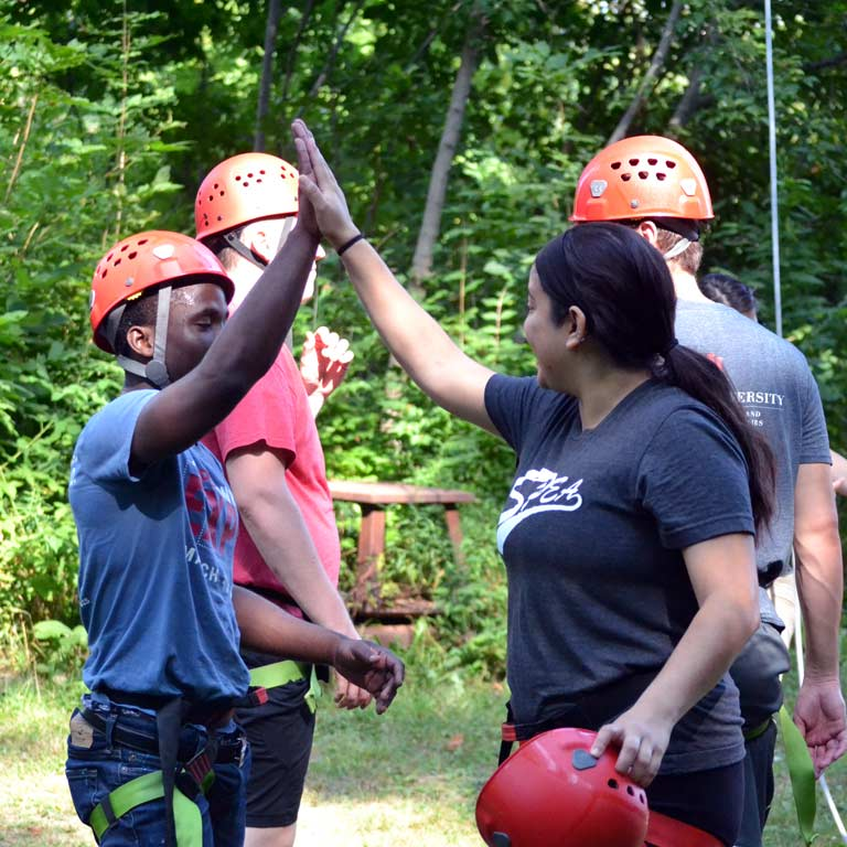 Students complete a ropes course and give each other high fives.