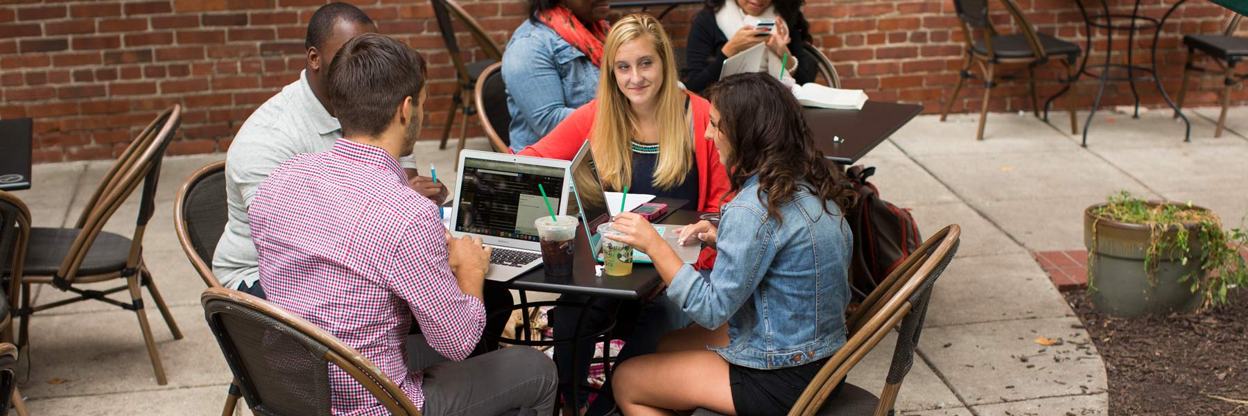 A group of students discuss college in an outdoor courtyard.