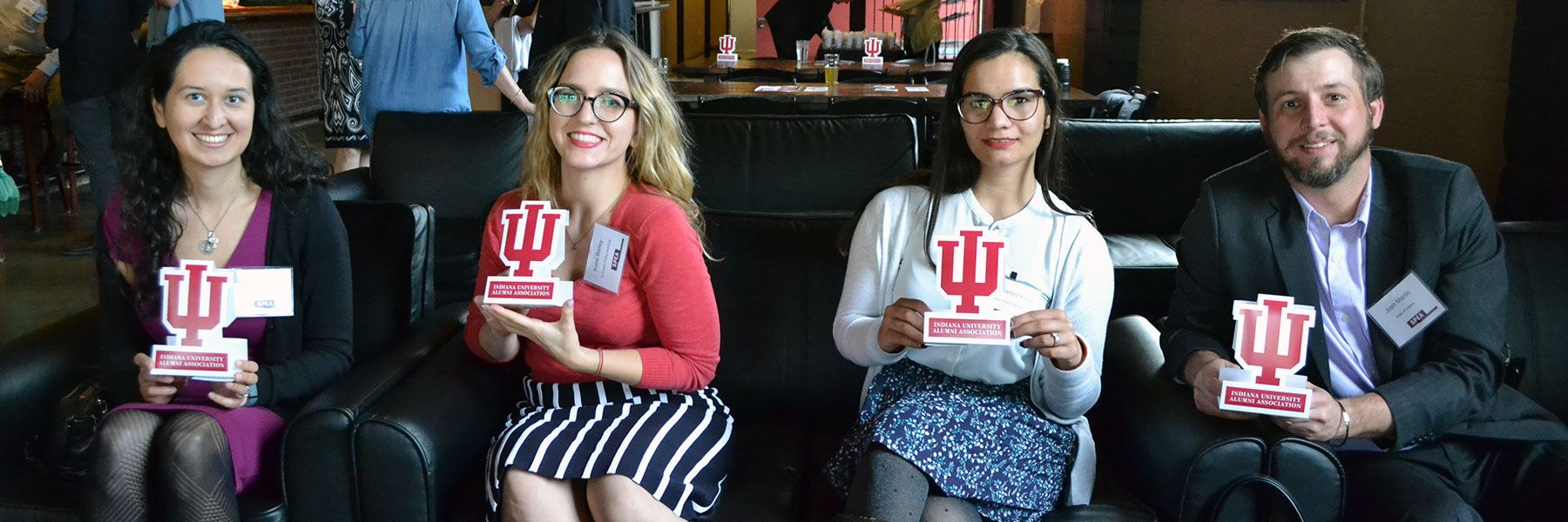 SPEA Alumni Association members smile and hold IU trident placards.