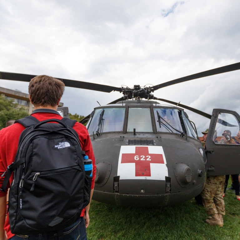 A student looks at a National Guard rescue helicopter.
