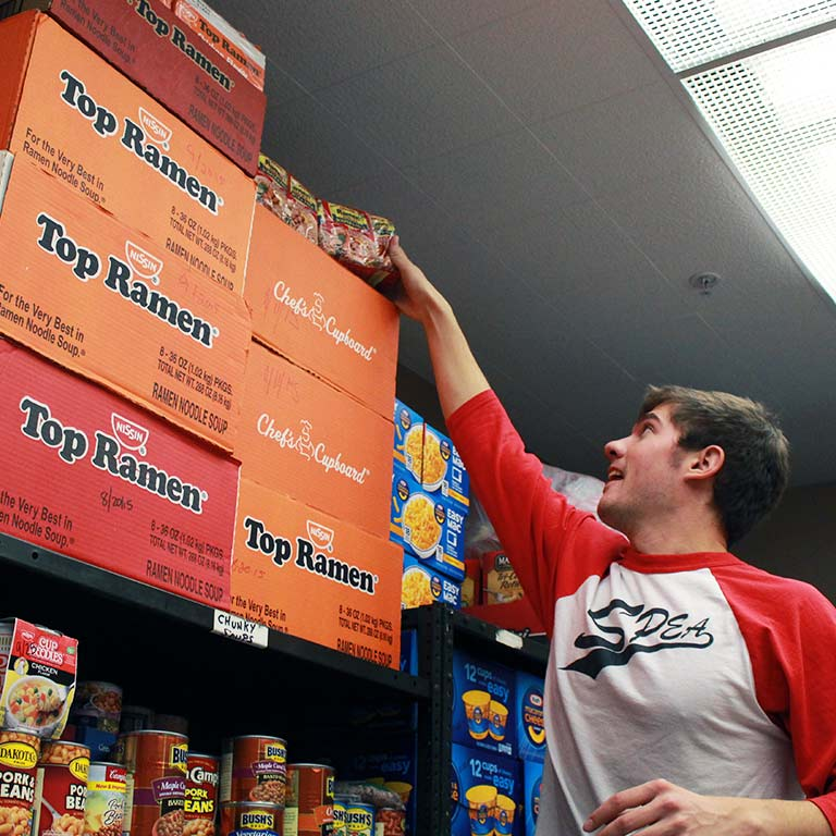 A SPEA student reaches for Ramen noodles as he helps stock a food bank.