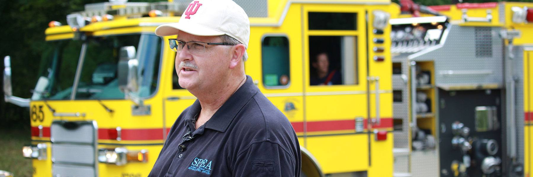 SPEA adjunct faculty member Stephen Davis stands in front of a fire truck.