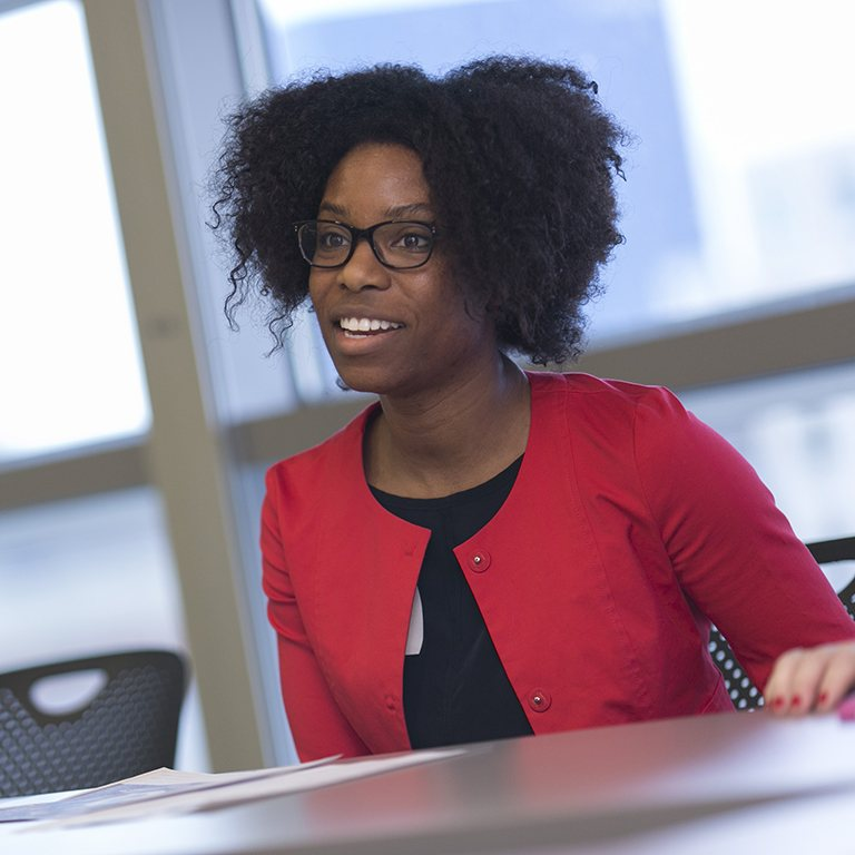A SPEA student sits at a table and smiles at the teacher.