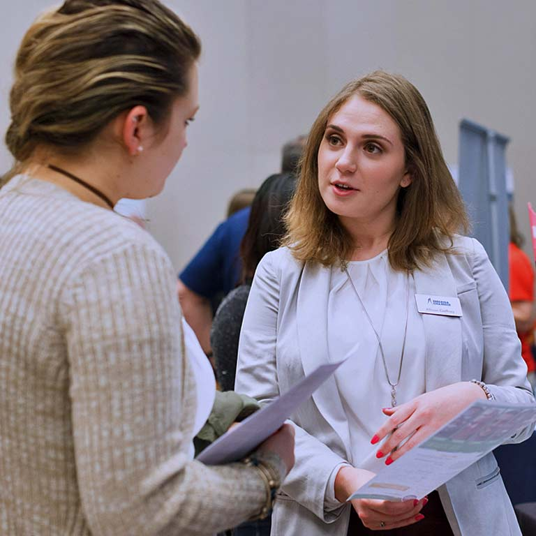 A nonprofit expo recruiter talks with a volunteer.