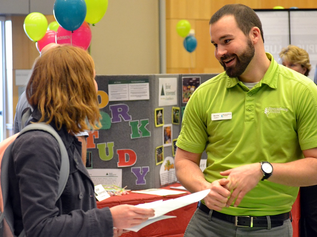 A SPEA student hands out information at a career fair.
