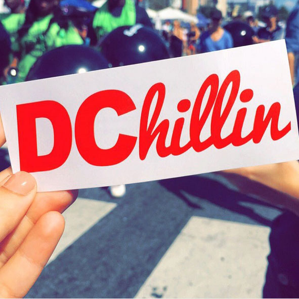 A student holds a bumper sticker that says 'DChillin'.